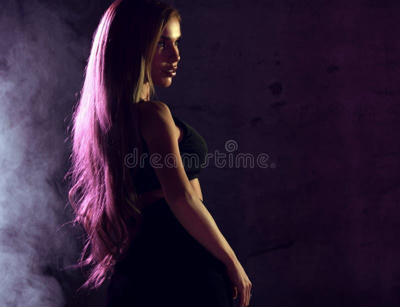 Mujer rubia atractiva hermosa que presenta en luz de neón azul y rosada en sujetador negro de la moda con humo imagen de archivo libre de regalías