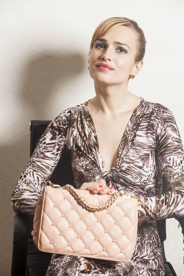 Mujer rubia atractiva hermosa que se sienta en silla imágenes de archivo libres de regalías