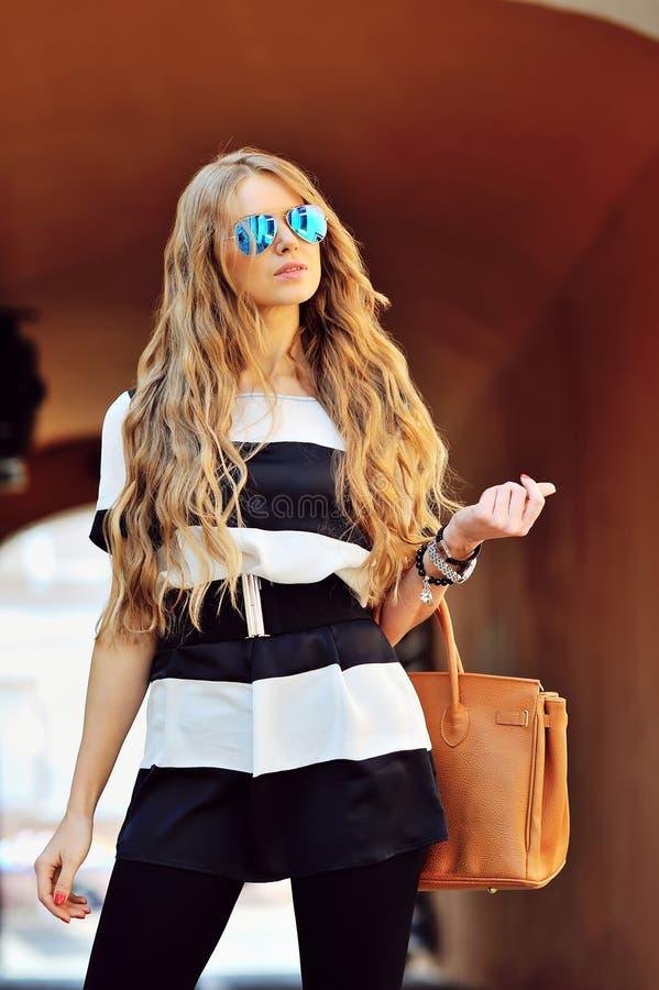 Mujer rubia atractiva joven con la presentación elegante del pelo al aire libre imagen de archivo libre de regalías
