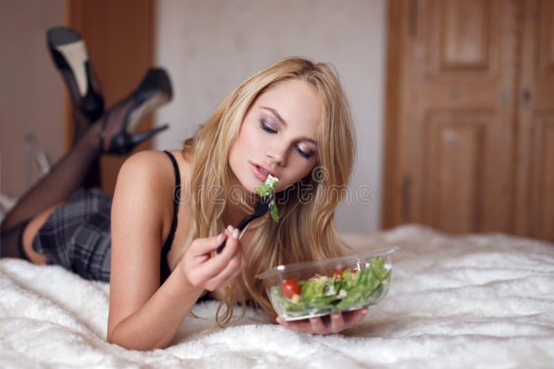 Mujer rubia atractiva que come la ensalada en cama imágenes de archivo libres de regalías