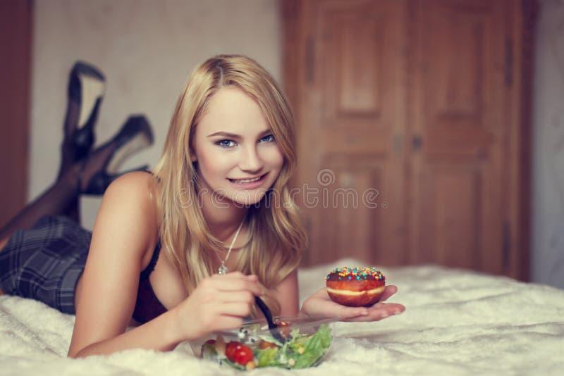 Mujer rubia atractiva que come la ensalada y el buñuelo en cama fotos de archivo