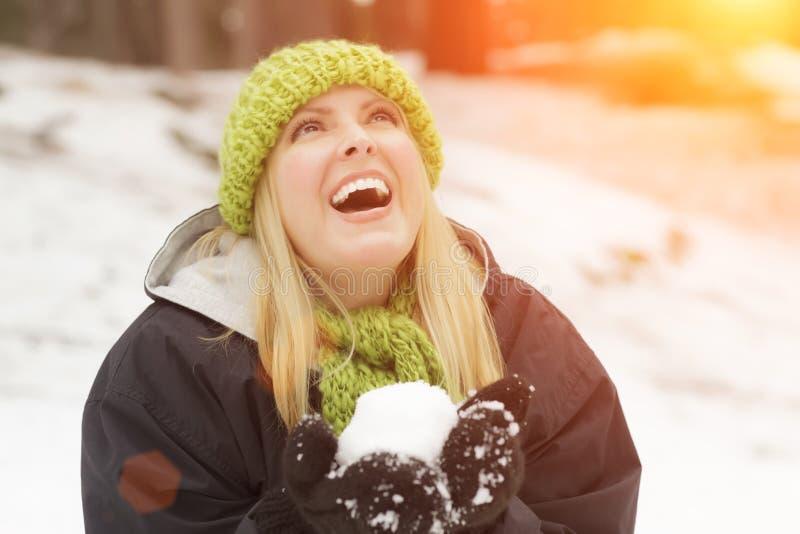 Mujer rubia atractiva que hace bolas de nieve y que juega en la nieve fotografía de archivo