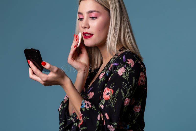 Mujer rubia atractiva que hace maquillaje con el polvo de cara en mejillas foto de archivo