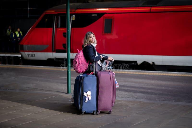 Mujer rubia atractiva que mira cansada y ocupada con muchos bolsos y equipaje una estación de tren con el tren rojo en fotos de archivo
