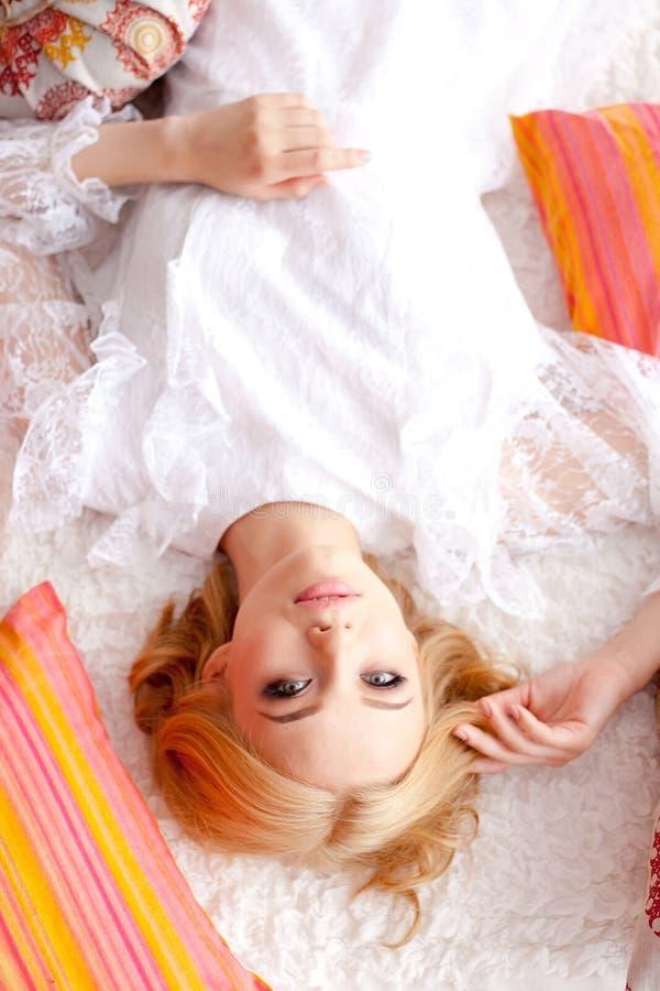 Mujer rubia atractiva que se acuesta en el sofá fotos de archivo libres de regalías