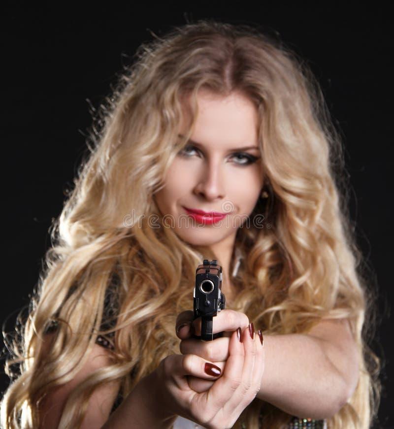 Mujer rubia atractiva que sostiene el arma en negro fotografía de archivo libre de regalías