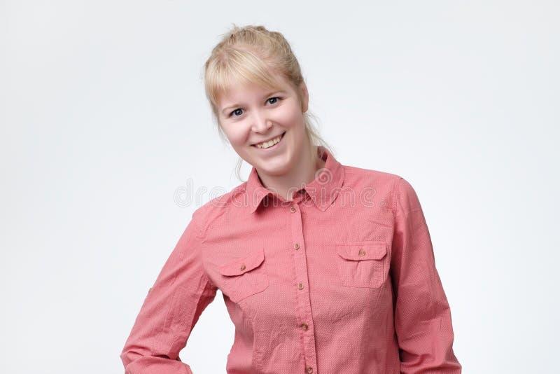 Mujer rubia atractiva sonriente wearsing la camisa rosada fotografía de archivo libre de regalías