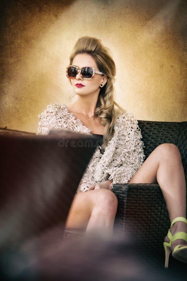Mujer rubia atractiva y atractiva con las gafas de sol que plantean provocativo sentarse en la silla, fondo marrón claro Hembra s imagen de archivo