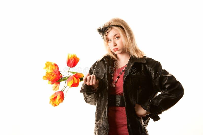 Mujer rubia bastante joven con las flores plásticas foto de archivo libre de regalías