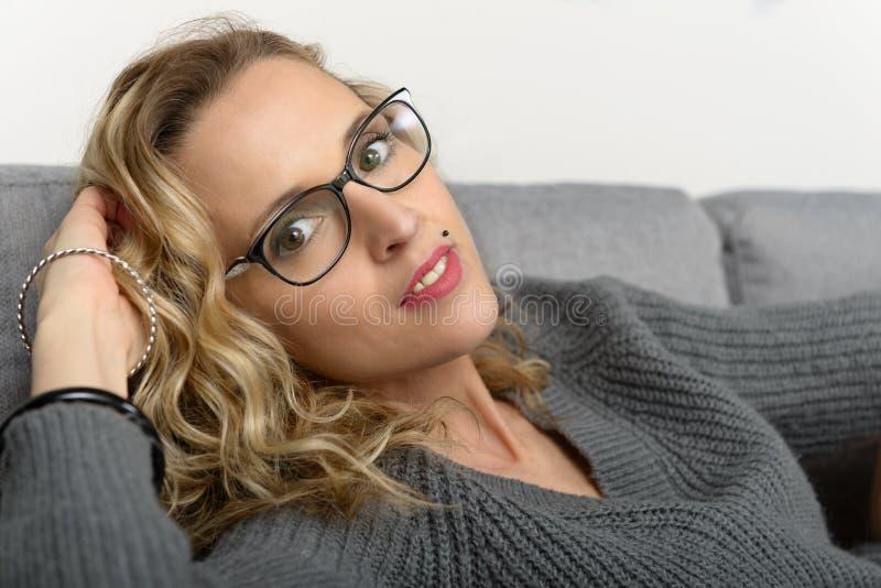 Mujer rubia bastante joven con las lentes que se relajan fotografía de archivo