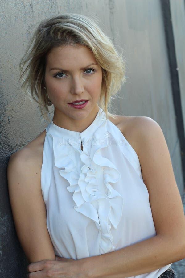 Mujer rubia bien proporcionada atractiva adorable en la blusa de seda blanca con clase que presenta en fondo gris foto de archivo libre de regalías