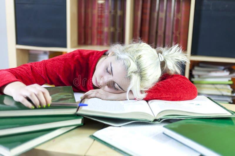 Mujer rubia cansada del estudiante que duerme en la tabla en casa imágenes de archivo libres de regalías