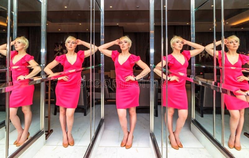 Mujer rubia caucásica que presenta en medio de instalaciones asombrosas del arte del espejo en interior del salón del hotel de Ri imagenes de archivo