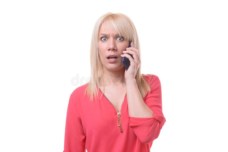 Mujer rubia chocada que escucha una llamada de teléfono fotos de archivo