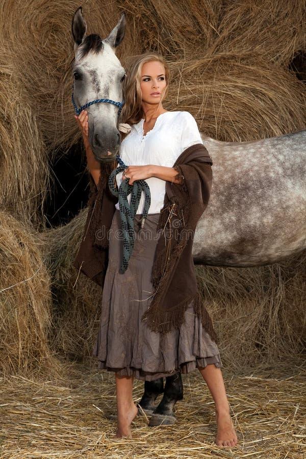 Mujer rubia con el caballo fotos de archivo