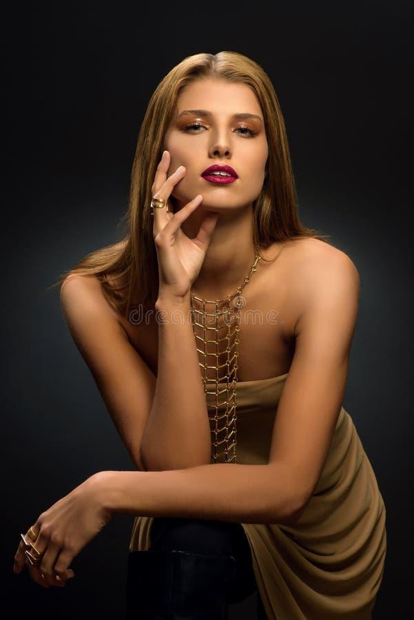 """Mujer rubia con el make†diseñado """"para arriba, el collar largo y muchos anillos en sus fingeres foto de archivo"""