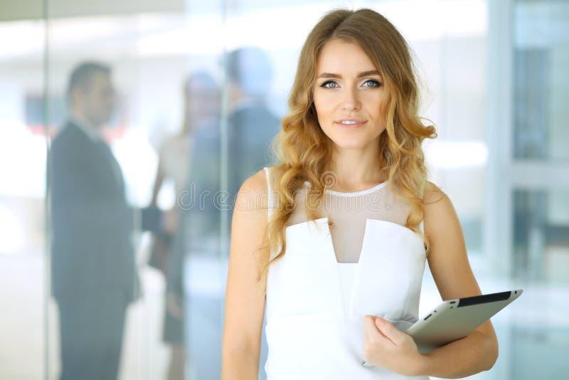 Mujer rubia con el ordenador del panel táctil que mira la cámara y que sonríe mientras que los hombres de negocios de la sacudida fotografía de archivo