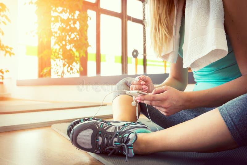 Mujer rubia con el teléfono elegante, descansando después de entrenamiento del gimnasio imagenes de archivo