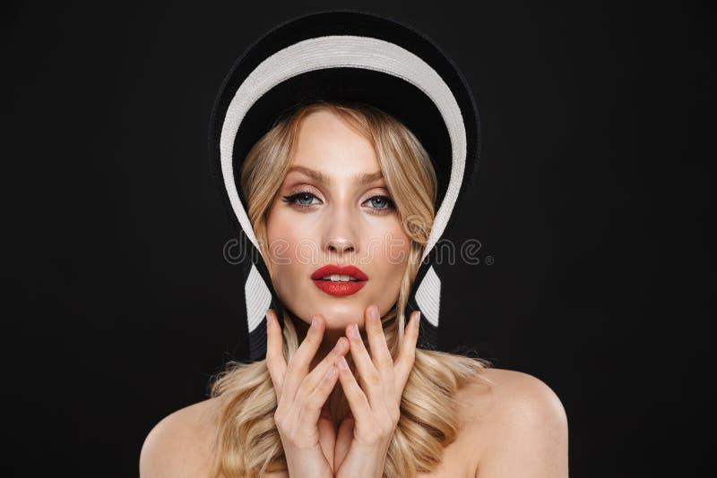 Mujer rubia con la presentación roja de los labios del maquillaje brillante aislada sobre el sombrero que lleva del fondo negro d foto de archivo libre de regalías
