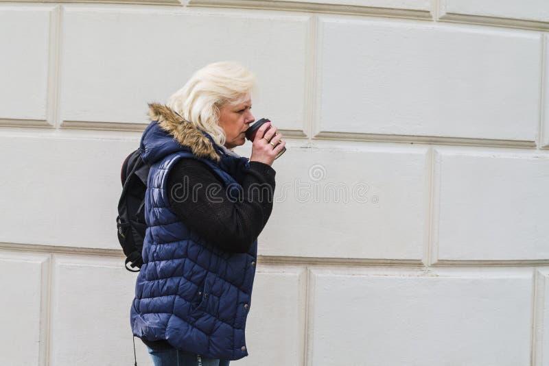 Mujer rubia con un café a ir imagen de archivo