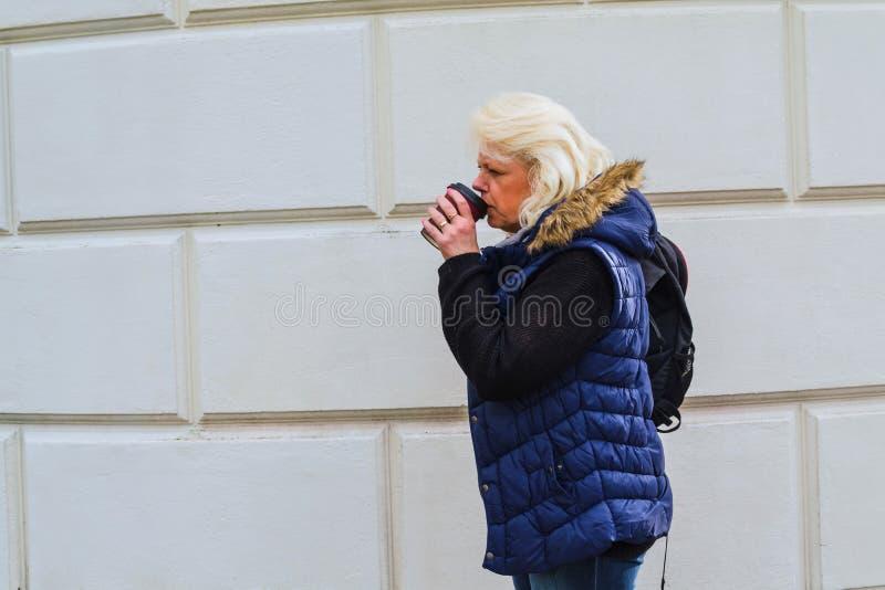 Mujer rubia con un café a ir imagen de archivo libre de regalías