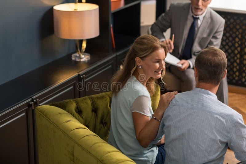 Mujer rubia contenta que mira blando su marido imagen de archivo