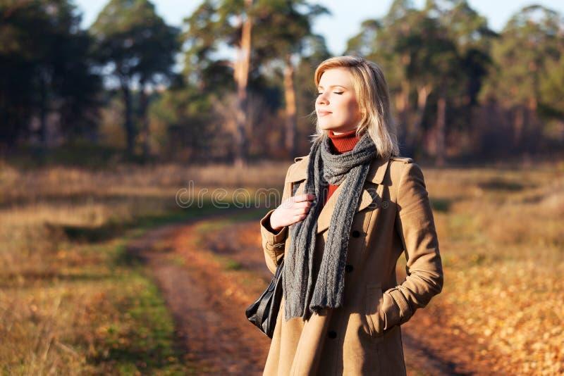 Mujer rubia contra un paisaje de la naturaleza del otoño fotos de archivo