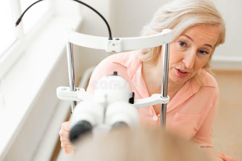 Mujer rubia curiosa en camisa rosada que pregunta a su doctor acerca del proceso de la comprobación imagen de archivo libre de regalías