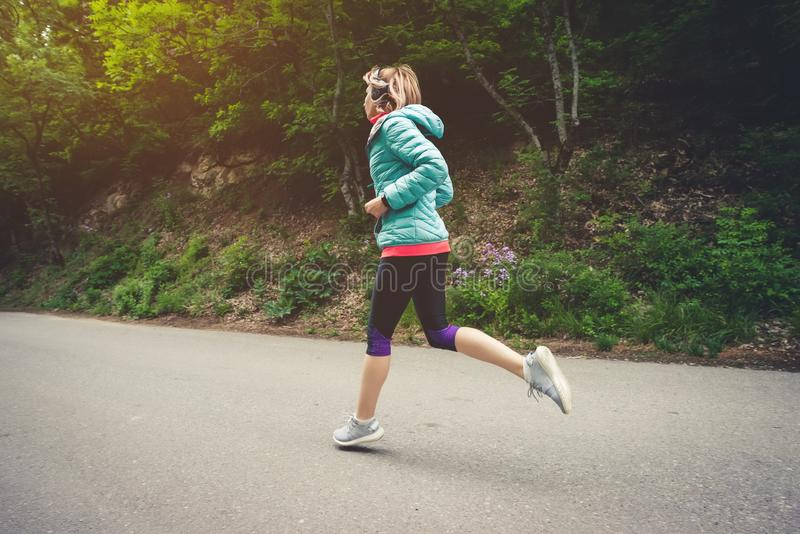 Mujer rubia de la aptitud joven en los auriculares que corren en el rastro caucásico del bosque de la mañana en luz del sol Vista fotos de archivo