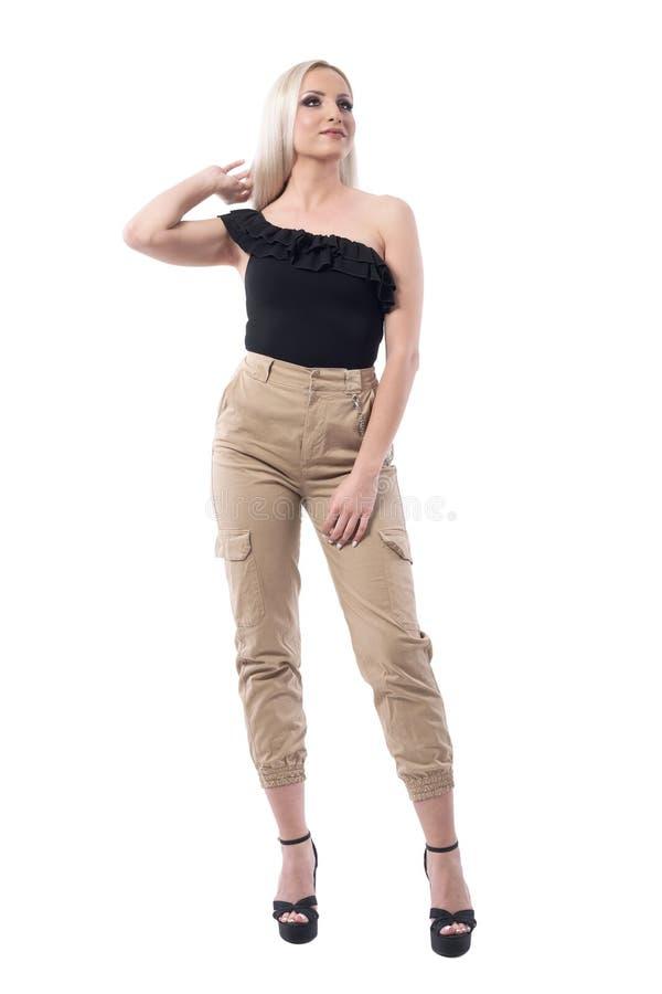 Mujer rubia de la calle de la mirada elegante atractiva del estilo que mira para arriba de ajuste del pelo con la mano foto de archivo