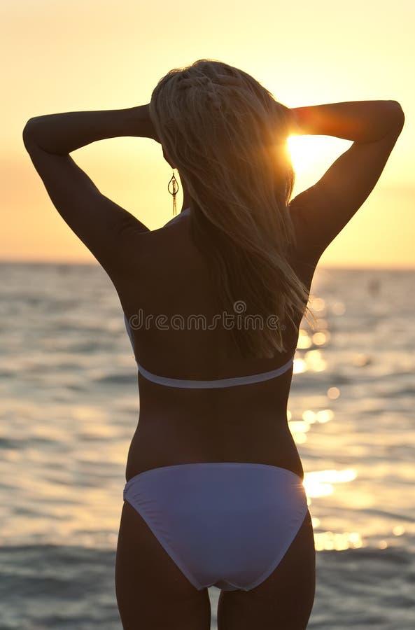 Mujer rubia de la visión trasera en la playa en bikiní en la puesta del sol