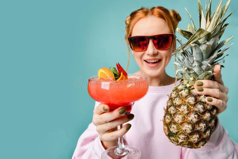 Mujer rubia de Laughting en gafas de sol rojas modernas con el cóctel del margarita de la fresa y una piña grande en el espacio d imagen de archivo