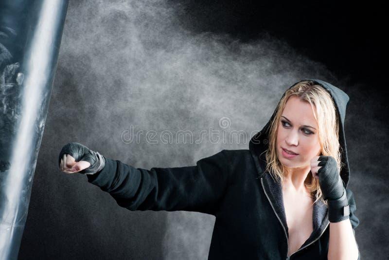 Mujer rubia del boxeo en bolso de perforación negro imagen de archivo
