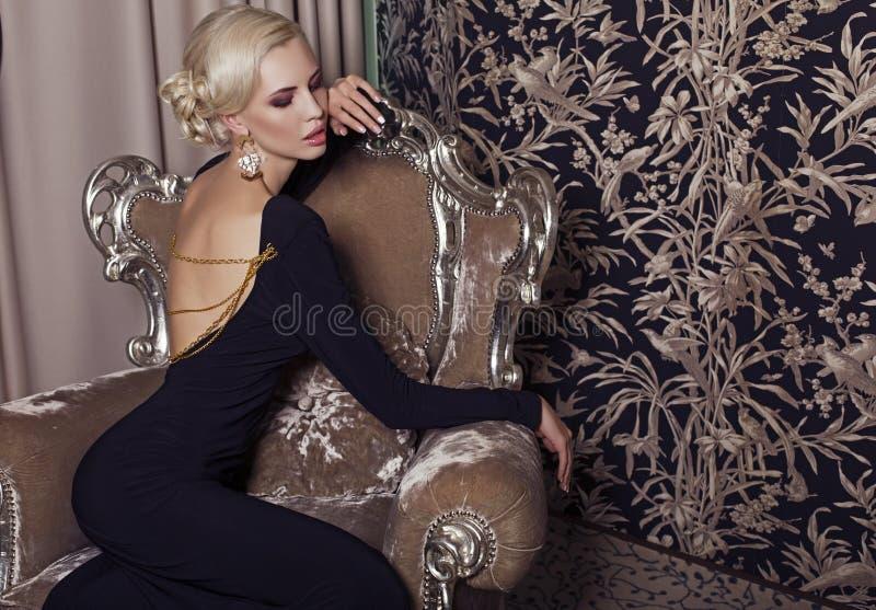 Mujer rubia del encanto atractivo en vestido negro elegante fotos de archivo