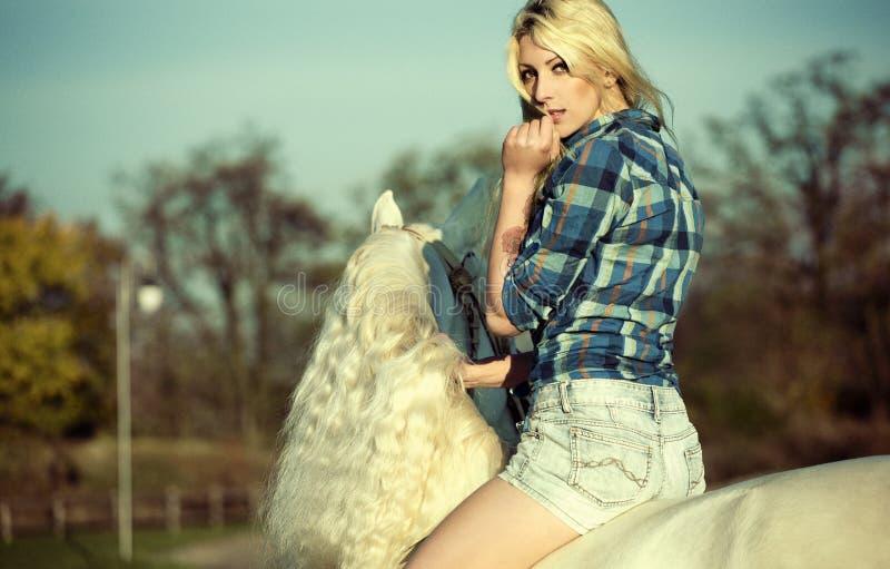 Mujer rubia del misterio que monta un caballo imagen de archivo