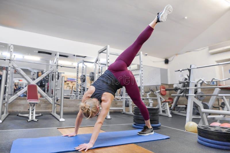 Mujer rubia deportiva adulta que estira el cuerpo mientras que hace ejercicios de la yoga en el gimnasio foto de archivo libre de regalías