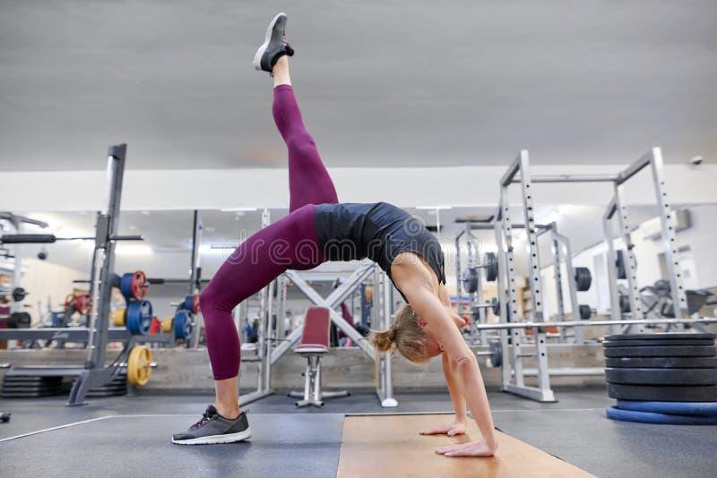Mujer rubia deportiva adulta que estira el cuerpo mientras que hace ejercicios de la yoga en el gimnasio imagenes de archivo