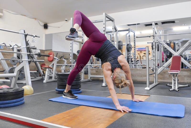 Mujer rubia deportiva adulta que estira el cuerpo mientras que hace ejercicios de la yoga en el gimnasio imágenes de archivo libres de regalías
