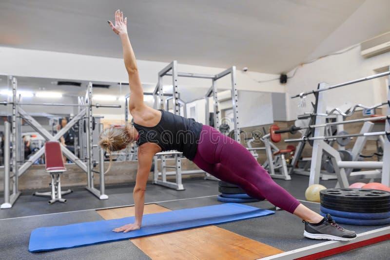 Mujer rubia deportiva joven que estira el cuerpo mientras que hace ejercicios de la yoga en el gimnasio fotografía de archivo