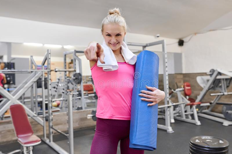 Mujer rubia deportiva joven que señala el finger a usted en gimnasio Concepto sano de la forma de vida del deporte de la aptitud  fotos de archivo
