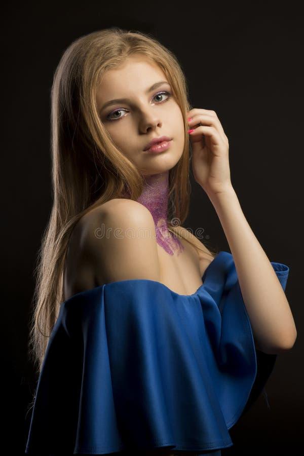 Mujer rubia elegante con el pelo enorme largo y el vestido azul con el NAK imagen de archivo libre de regalías