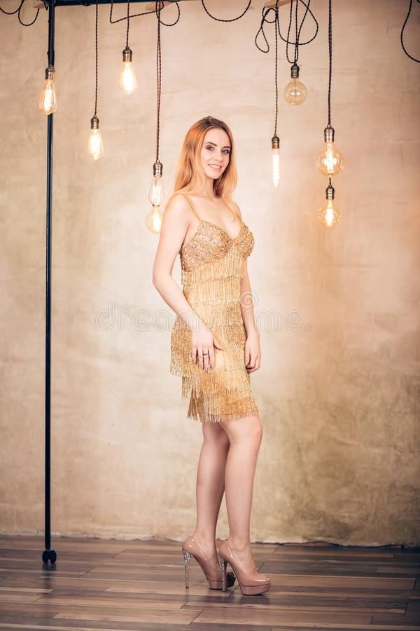 Mujer rubia elegante del retrato integral en vestido corto del oro en el estudio Partido, día de fiesta, celebración, Año Nuevo,  fotos de archivo