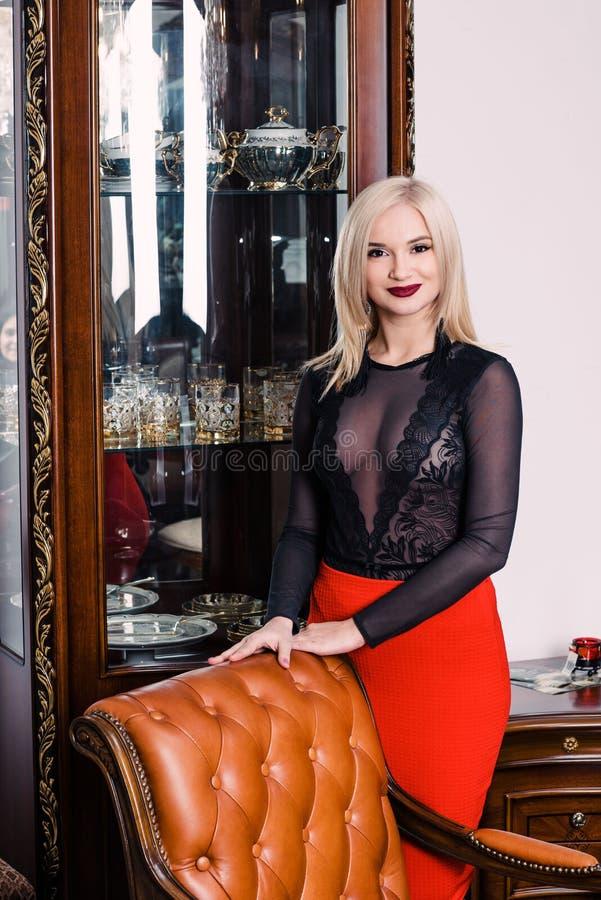 Mujer rubia elegante elegante en el interior rico de la belleza, vestido negro que lleva imagen de archivo