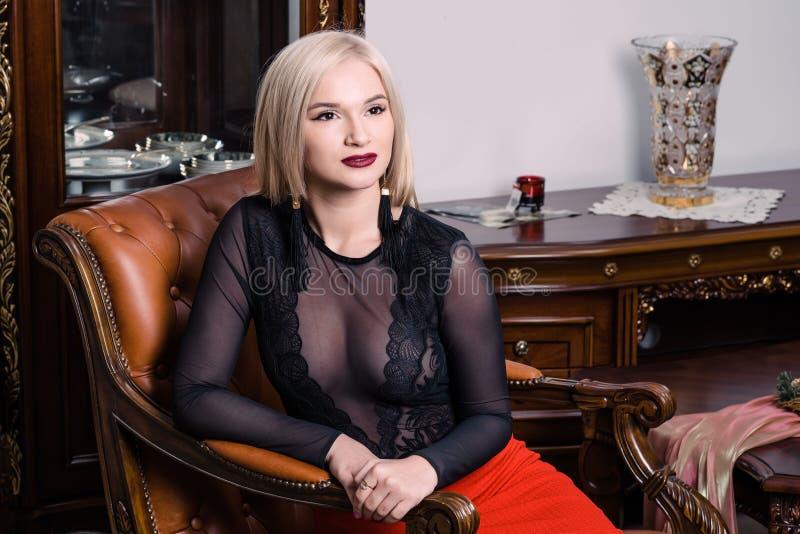 Mujer rubia elegante elegante en el interior rico de la belleza, vestido negro que lleva fotografía de archivo