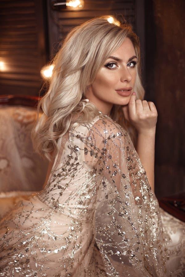 Mujer rubia elegante en el vestido beige que presenta en el sofá de lujo en interior real Novia sensual hermosa de la moda con el fotografía de archivo