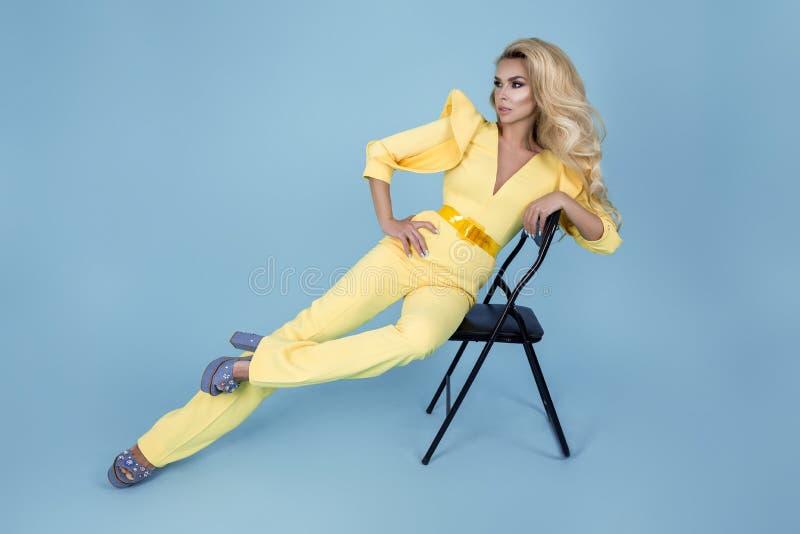 Mujer rubia elegante en mono amarillo elegante y accesorios de moda en fondo del color Modelo de moda hermoso en azul fotografía de archivo libre de regalías