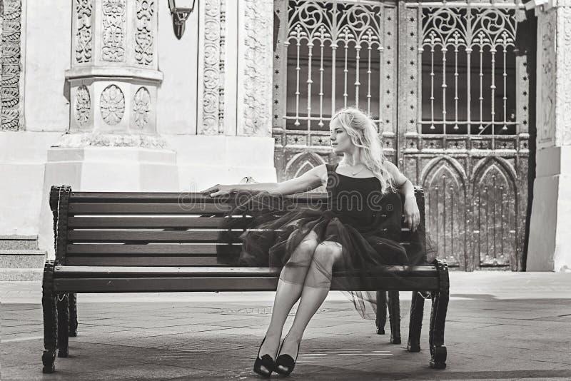 Mujer rubia elegante joven hermosa en el vestido negro que se sienta en a fotografía de archivo