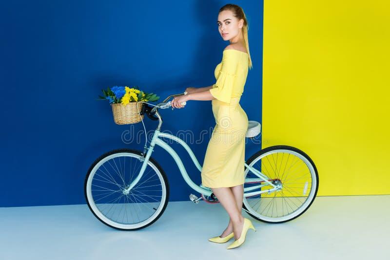 Mujer rubia elegante que presenta en bicicleta con las flores en cesta en azul fotos de archivo libres de regalías