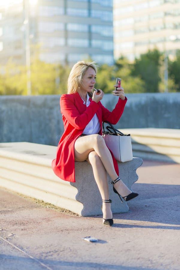 Mujer rubia elegante que usa su barra de labios que se sienta en un banco y un u imágenes de archivo libres de regalías