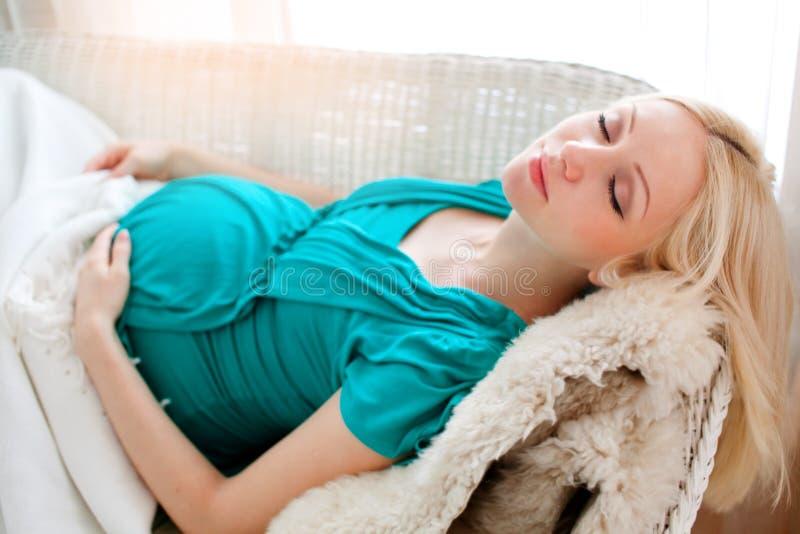 Mujer rubia embarazada que se relaja en el sofá, libro de lectura, soñando, imágenes de archivo libres de regalías